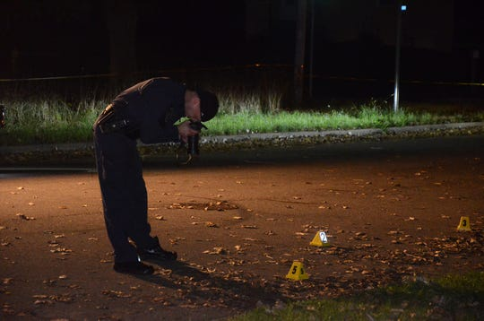 Crime Technician Kevin Stansbery photographs evidence at the scene of a shooting in Claude Evans Park Tuesday, Oct. 9.