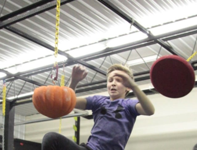 Evan completing a lache from a UFO to a pumpkin hold during a competition at Hybrid Fitness in Buffalo.