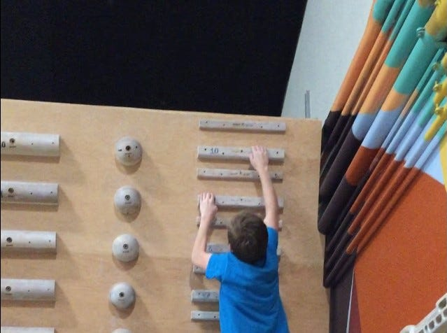 Evan shown here training on a campus board at a rock climbing gym in Oceanside, California during a family vacation.