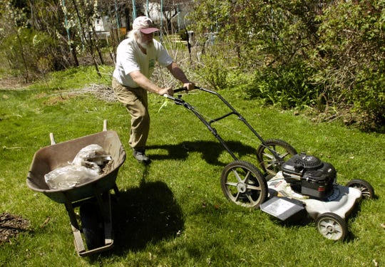 Dick Andrus mows his grass at his Binghamton home in 2006.