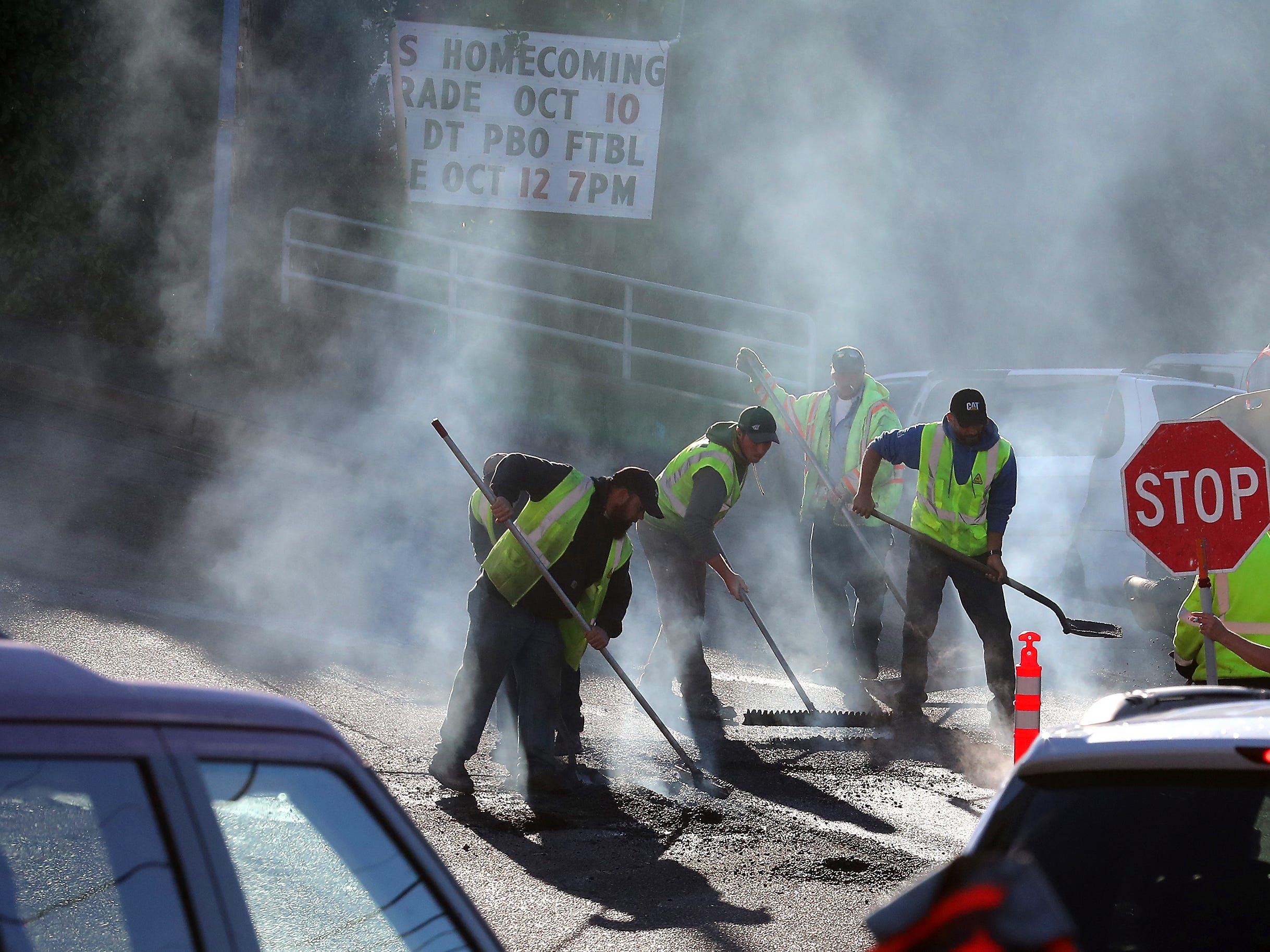 Steam rises as crews lay a fresh patch of asphalt on Front Street in downtown Poulsbo on Tuesday, October 9, 2018.