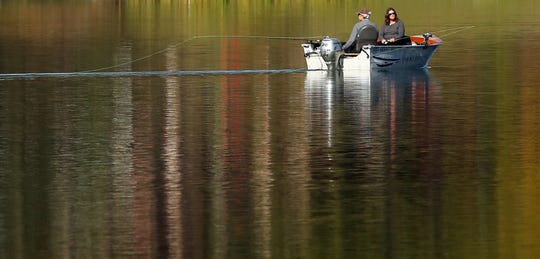 A duo fishes from a small boat gliding through the reflective waters of Kitsap Lake in Bremerton on Wednesday, October 10, 2018.
