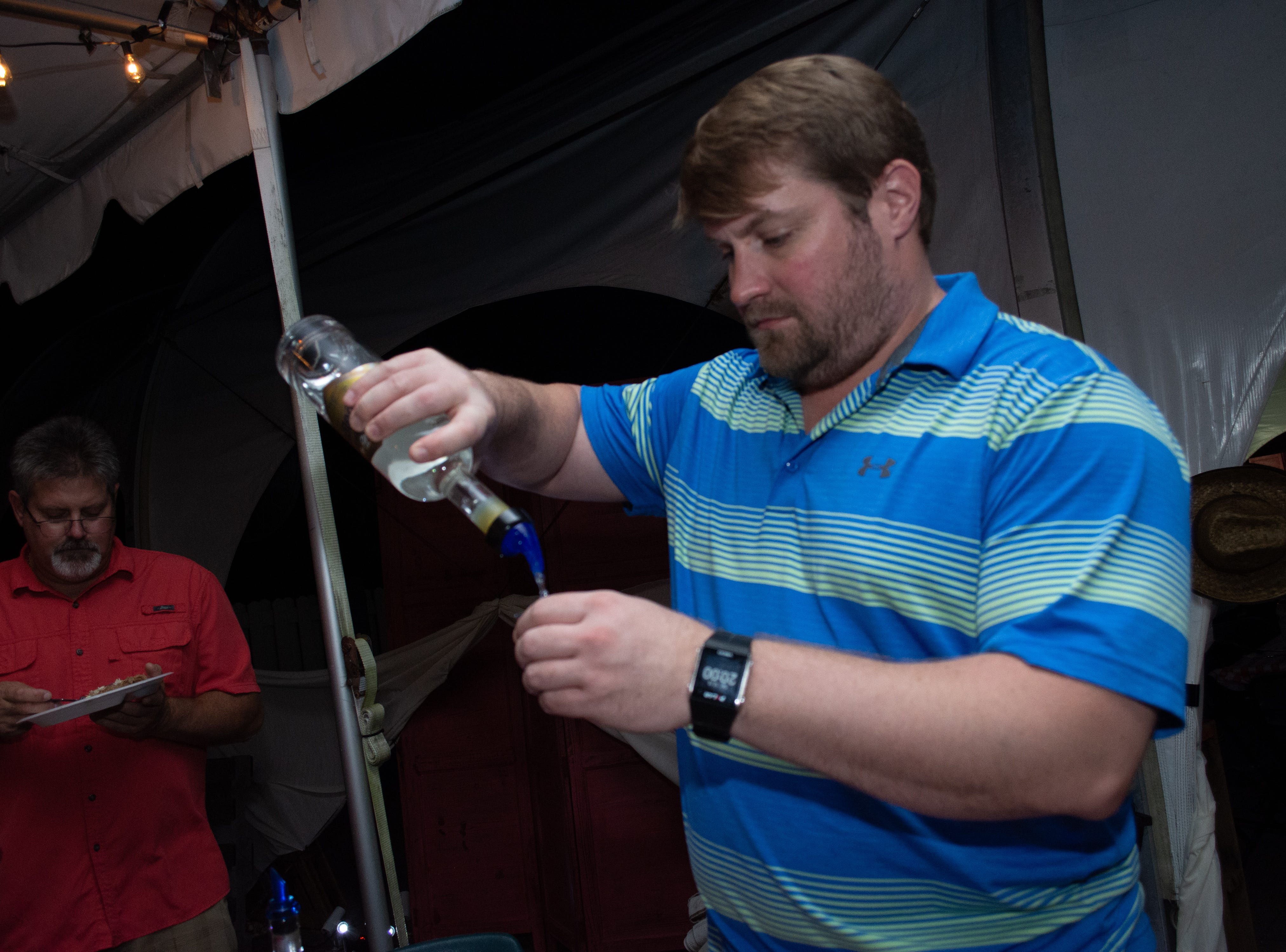 Andy Konzen with Honey Lane Distillery pours a shot. Arron Lampkin/For FLORIDA TODAY