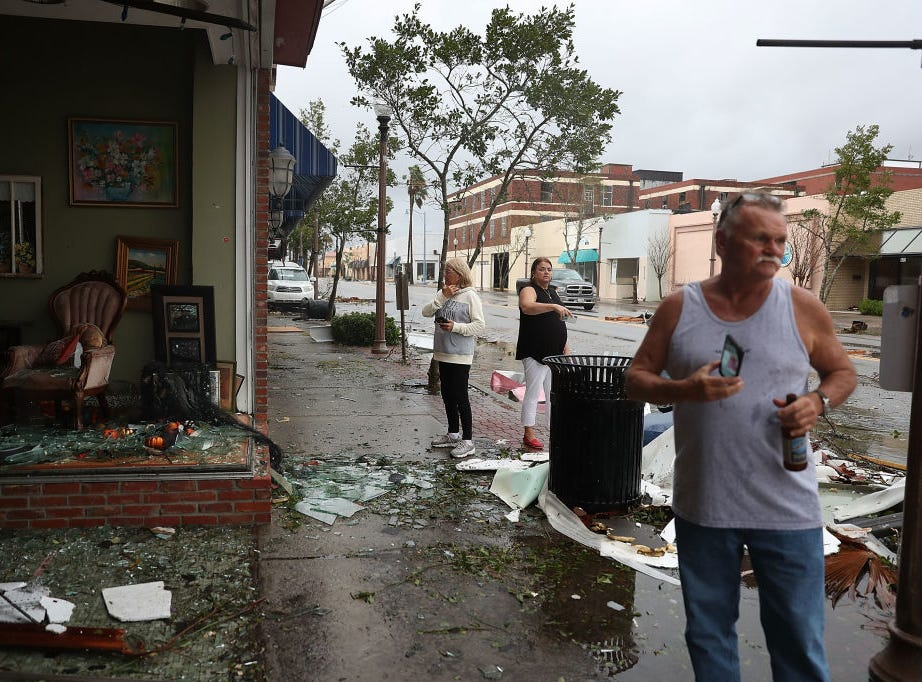 PANAMA CITY, FL - OCTOBER 10:  People walk past damaged stores after hurricane Michael passed through the downtown area on October 10, 2018 in Panama City, Florida. The hurricane hit the Florida Panhandle as a category 4 storm.  (Photo by Joe Raedle/Getty Images)