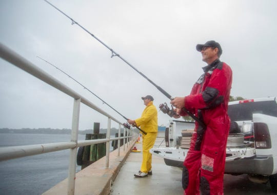 Bill Wimett, left, and John Welch get a little fishing in at the St. Andrew Marina before Hurricane Michael smashes into the coast.