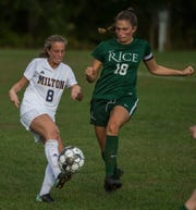 Milton #8 Molly Loucy hits the ball just ahead of Rice #18 Abby McKeown during their girls high school soccer game in South Burlington on Wednesday, Oct. 10, 2018. Milton won, 2-1.