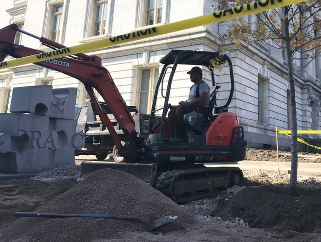 Shon Dickerson, of Richmond-based Anything Grows landscapers, shifts gravel and stone on the northeast corner of the Chittenden County Courthouse on Wednesday, Oct. 10, 2018.