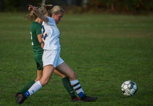 Milton #22 Tatum Shappy squeezes out Rice #2 Hannah Shepard during their girl's high school soccer game in South Burlington on Wednesday, Oct. 10, 2018. Milton won, 2-1.