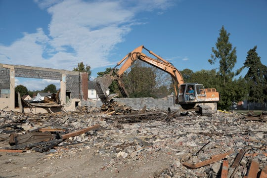 A bulldozer works on demolishing the last standing walls of the stage and gym of Worthington Elementary Wednesday morning in Chillicothe, Ohio.