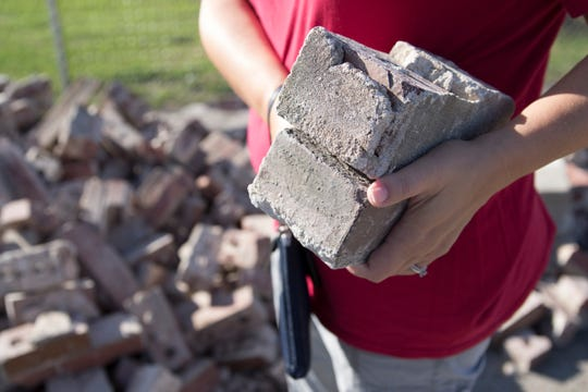 Kate Drees collects a couple of bricks being given out during the demolition of Worthington Elementary Wednesday morning in Chillicothe, Ohio. Drees was PTO president when her two sons, now 13 and 17, attended Worthington.