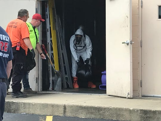 Members of the Jackson County Emergency Response Team clean the spill of a chemical in the Pike County Service Center on Wednesday morning. The building was evacuated as a precaution and is expected to reopen on Thursday.