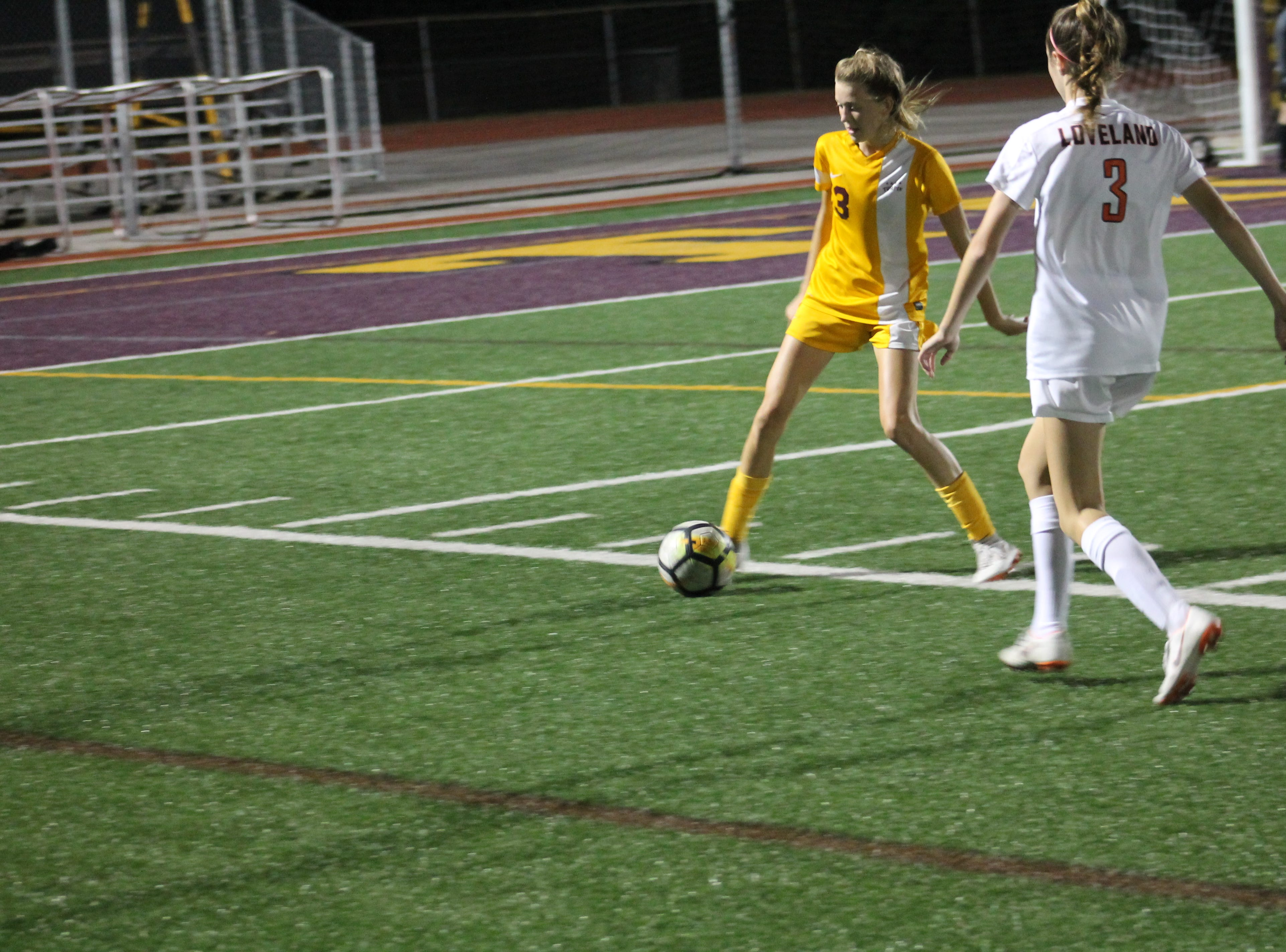 Turpin freshman Claire Klimkowski tries to clear the ball away from Loveland's Allison Reynolds