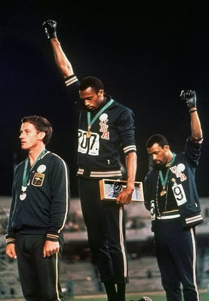 """In this Oct. 16, 1968, file photo, extending gloved hands skyward in racial protest, U.S. athletes Tommie Smith, center, and John Carlos stare downward during the playing of """"The Star-Spangled Banner"""" after Smith received the gold and Carlos the bronze medal in the 200 meter run at the Summer Olympic Games in Mexico City. Australian silver medalist Peter Norman is at left."""