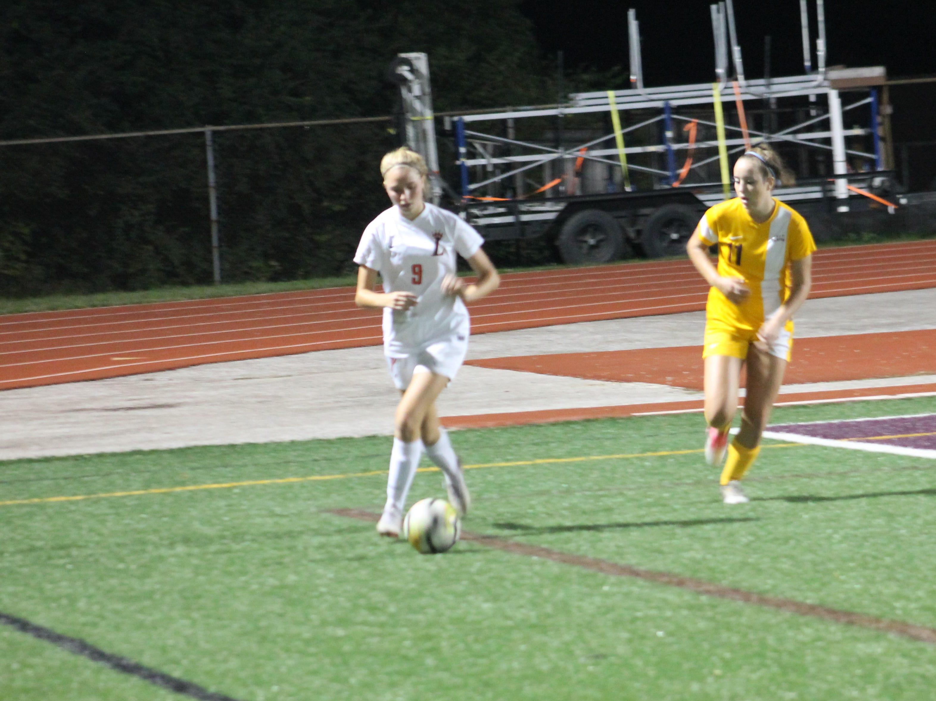 Loveland sophomore Catrin Palmer dribbles upfield with Turpin's Mimi Pinckney in pursuit