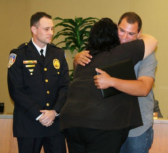 Tyler Tacy gets a hug from Fairfield dispatcher Tracy Brown as police Chief Stephen Maynard looks on.