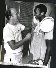 JULY 13, 1969: Olympic sprint champion Tommie Smith, right, gets his gear from equipment manager Tom Gray.