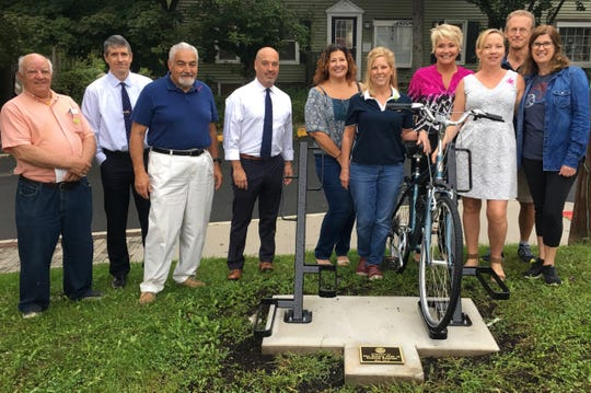 Rotarians Joe Tapp, James Keehbler, President Chris Knoll, Past Presidents MaryBeth Sullivan and Megan Jones-Holt and Amy DeVita, Mayor Janice Kovach, and Clinton Bicycle Shop Owners Gardner and Rachel Berridge.