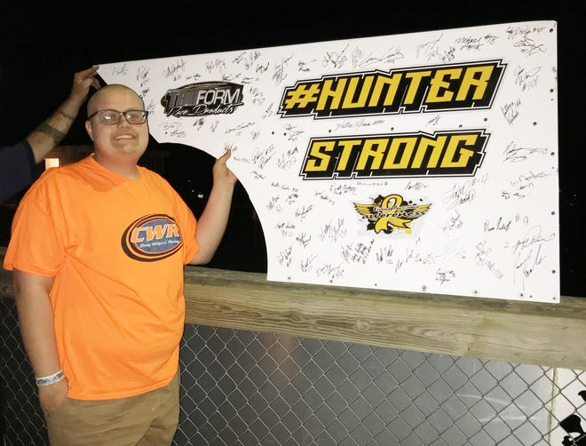 Hunter Bickle poses with a sign at Hilltop Speedway in Millerburg during Hunters Race. All the drivers autographed the sign for Hunter who has been successfully fighting Erwing's scarcoma. He will travel to California later this month to attend TwitchCon 2018, thanks to the Make-A-Wish Foundation.