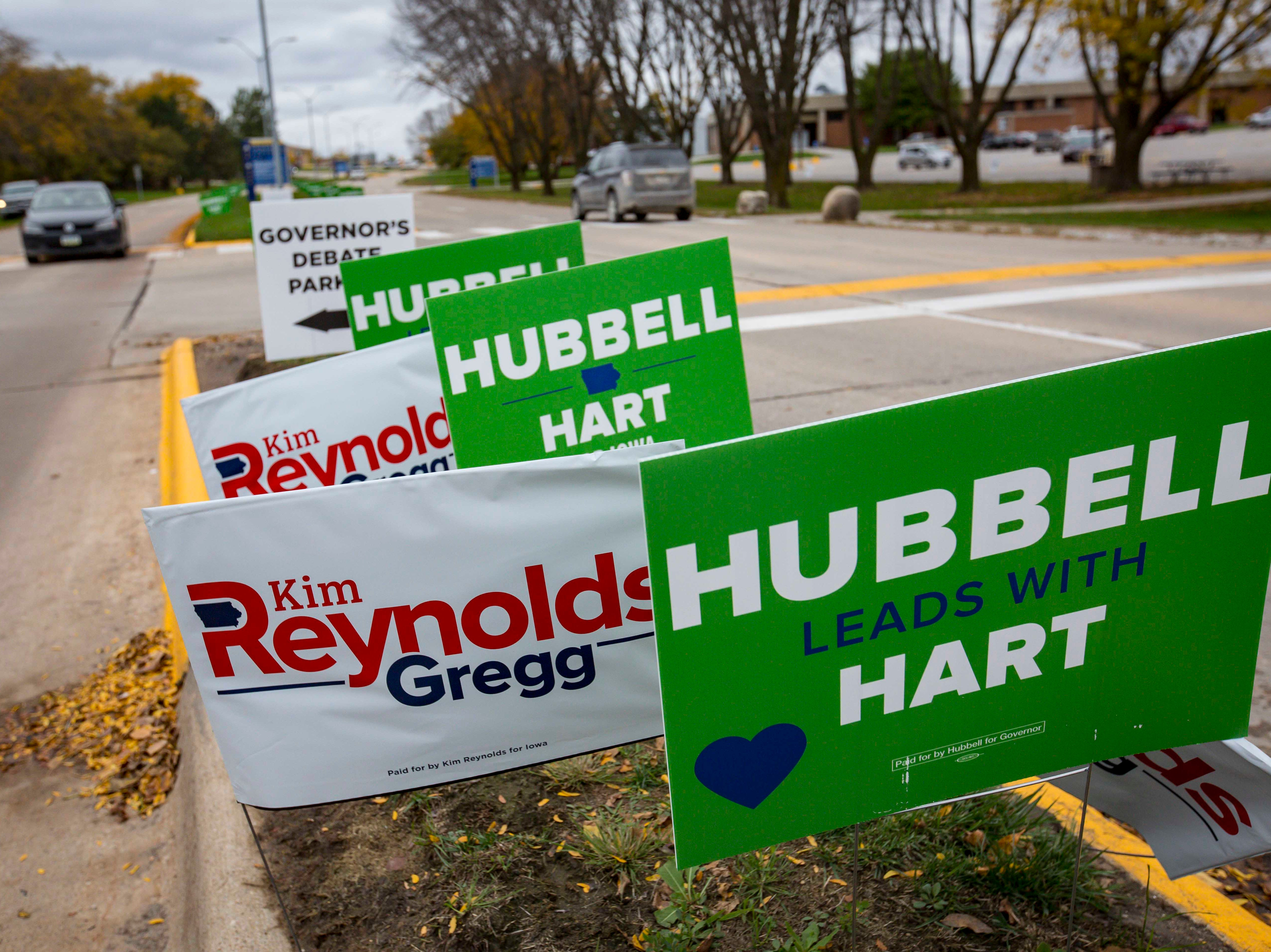 Campaign signs for Republican Iowa Gov. Kim Reynolds and Democratic challenger Fred Hubbell Wednesday, Oct. 10, 2018, at Des Moines Area Community College in Ankeny, Iowa.