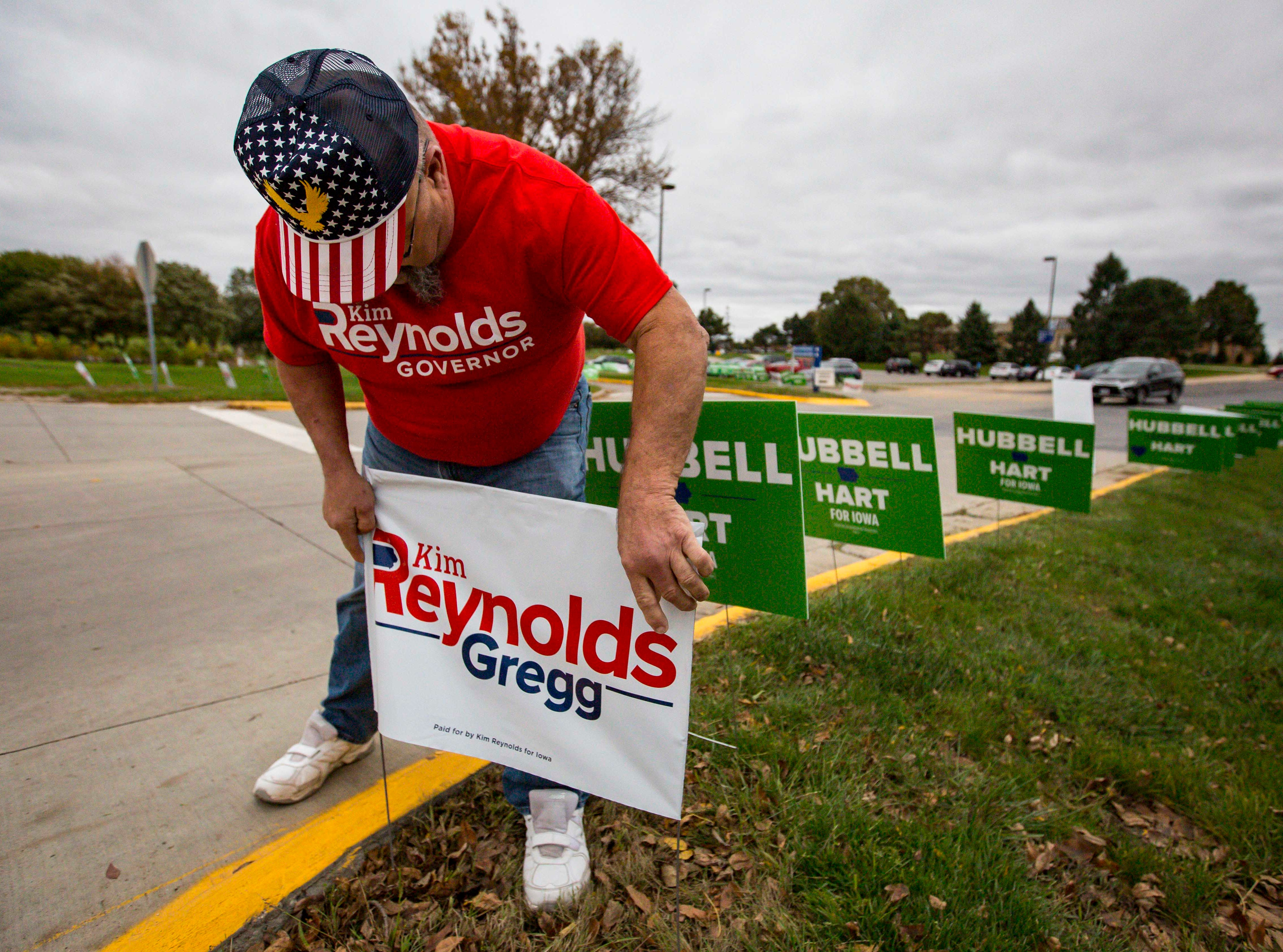 Bykermark Carver places campaign signs for Republican Iowa Gov. Kim Reynolds before a debate with Democratic challenger Fred Hubbell Wednesday, Oct. 10, 2018, at Des Moines Area Community College in Ankeny, Iowa.