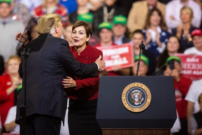 Iowa Governor Kim Reynolds joins President Donald Trump on stage during a rally at the Mid-America Center on Tuesday, Oct. 9, 2018, in Council Bluffs.