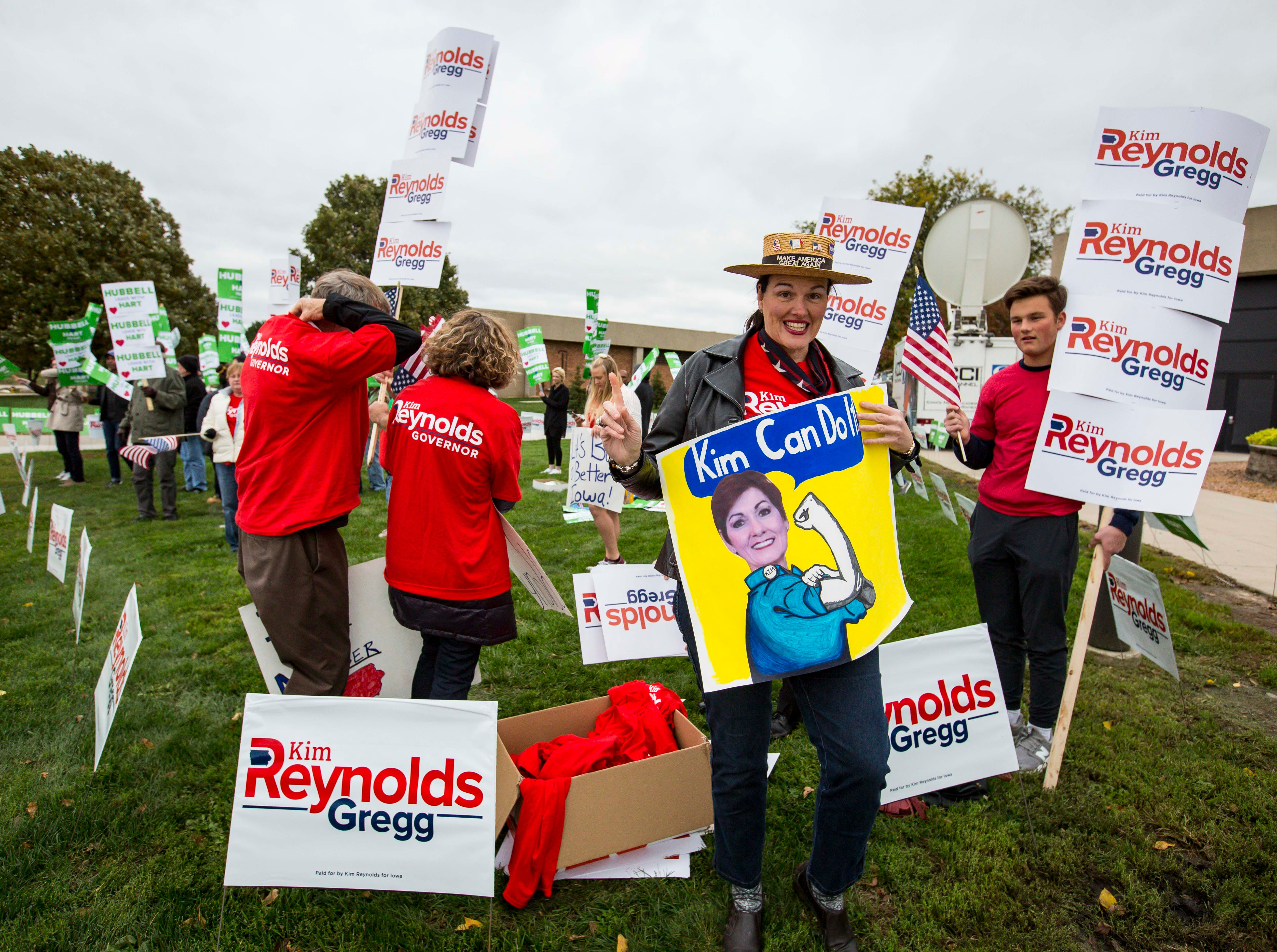 Supporters of Republican Iowa Gov. Kim Reynolds and Democratic challenger Fred Hubbell cheer before the debate Wednesday, Oct. 10, 2018, at Des Moines Area Community College in Ankeny, Iowa.