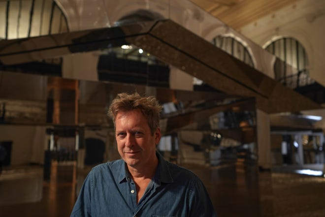 """LA artist Doug Aitken poses with his mirrored house for his exhibit """"Mirage Detroit"""" on display in the lobby of the State Savings Bank in downtown Detroit on Tuesday, October 9, 2018."""