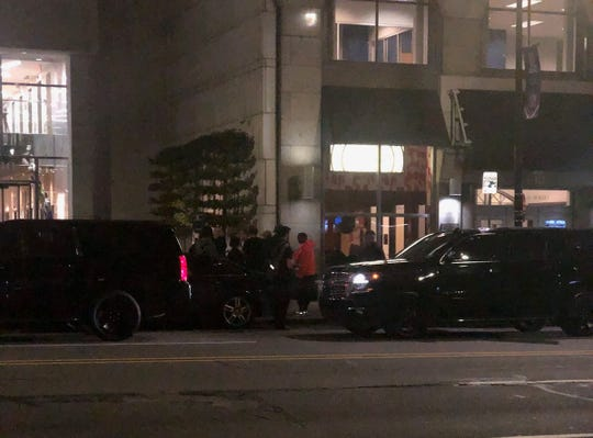 Kanye West (orange hoodie) was photographed by an onlooker Tuesday night outside the Federal Reserve Building in Detroit.
