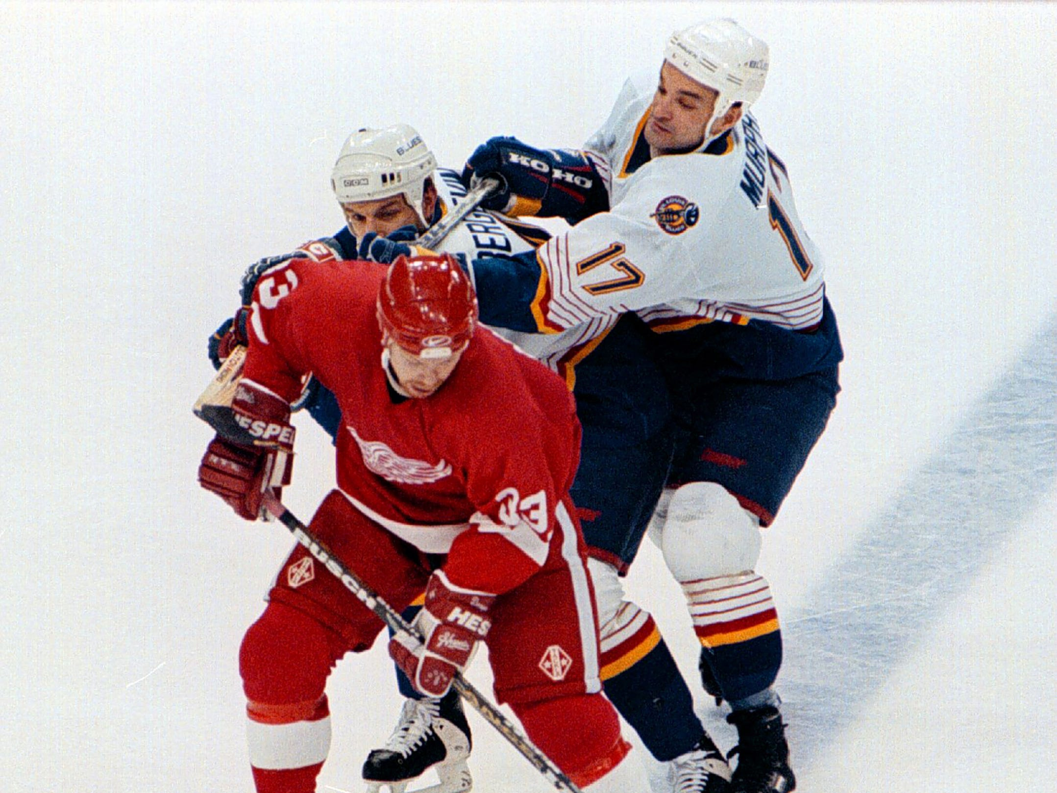 Blues #4 Marc Bergevin and #17 Joe Murphy trying to defense Wings #33 Kris Draper in the lst period.