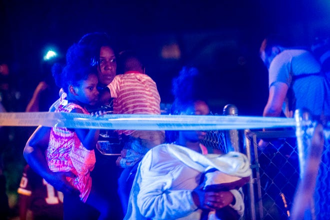 Family members leave the scene as Flint police investigate after a 7-year-old girl was shot and killed on Tuesday, Oct. 9, 2018, on the north side of Flint, Mich. No suspect information was immediately available.