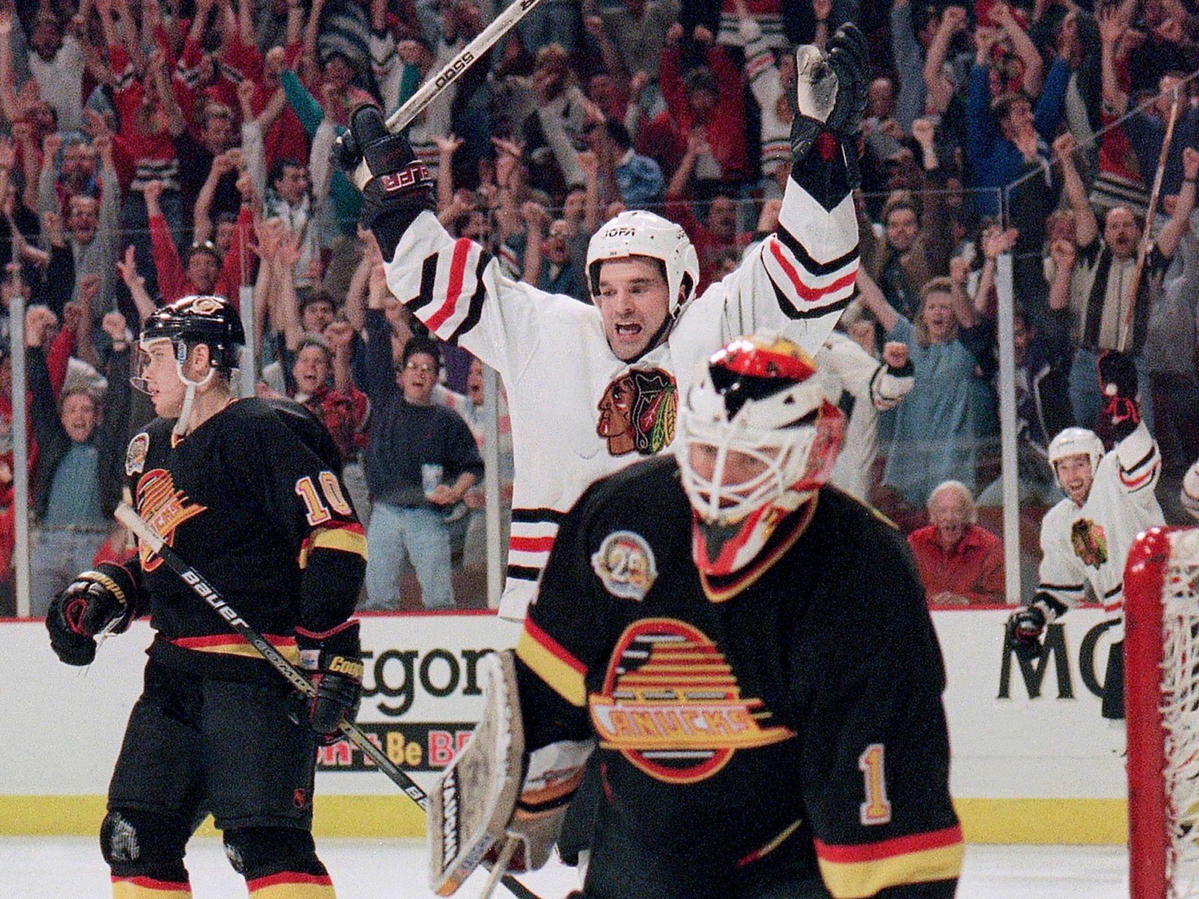 The Chicago Blackhawks' Joe Murphy celebrates over Vancouver Canucks goalie Kirk McLean after his overtime goal in the second-round playoff game, Sunday, May 21, 1995 in Chicago. The Blackhawks won 2-1 to take a 1-0 lead in the best-of-seven series.
