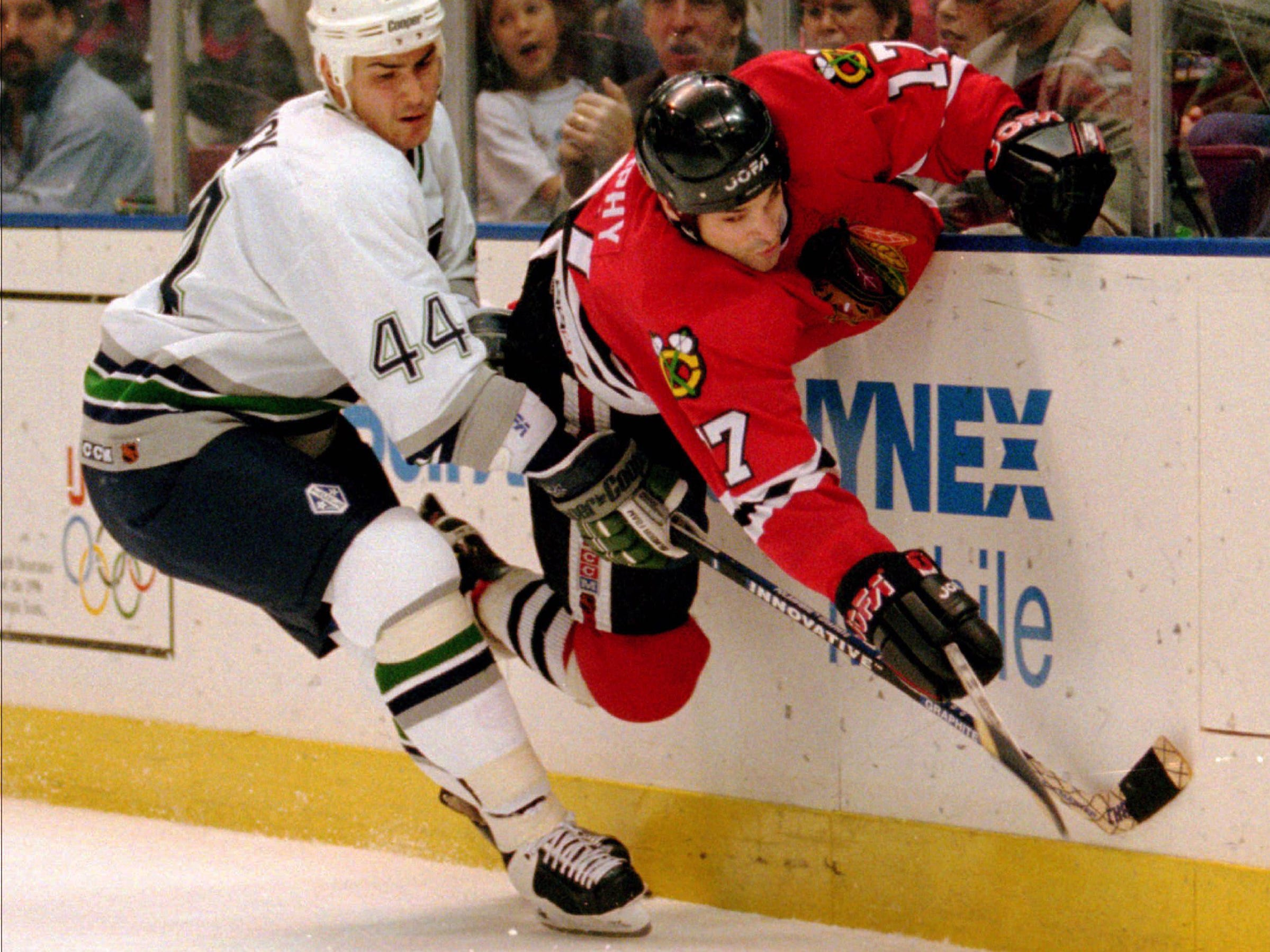 Chicago Blackhawks winger Joe Murphy, right, goes flying against the boards as he fights for the puck with Hartford Whalers defenseman Gerald Diduck (44) behind the Whalers net during first period NHL action at the Hartford Civic Center, Saturday, Oct. 14, 1995.   HF104