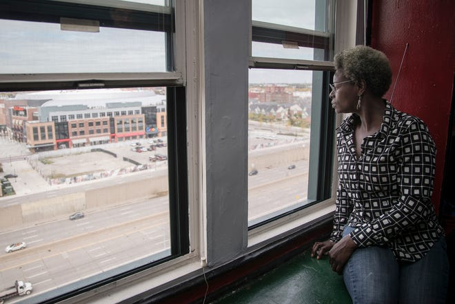 Harrietta Watson looks out from the windows of the apartment she shares with boyfriend Brian Demarest (not in the photo) at Park Avenue Hotel in Detroit, Tuesday, October 9, 2018.