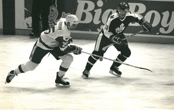 "Joe Murphy (left), racing Newmarket's Greg Hotham for a loose puck. Murphy  scored a goal and two assists as the Adirondack Red Wings beat the Saints, 7-4, in an American Hockey League game at Joe Louis Arena. Adirondack coach Bill Dineen said the former No. 1 draft choice's ""work ethic has improved 1,500 percent"" since the Red Wings sent him to their top farm club."