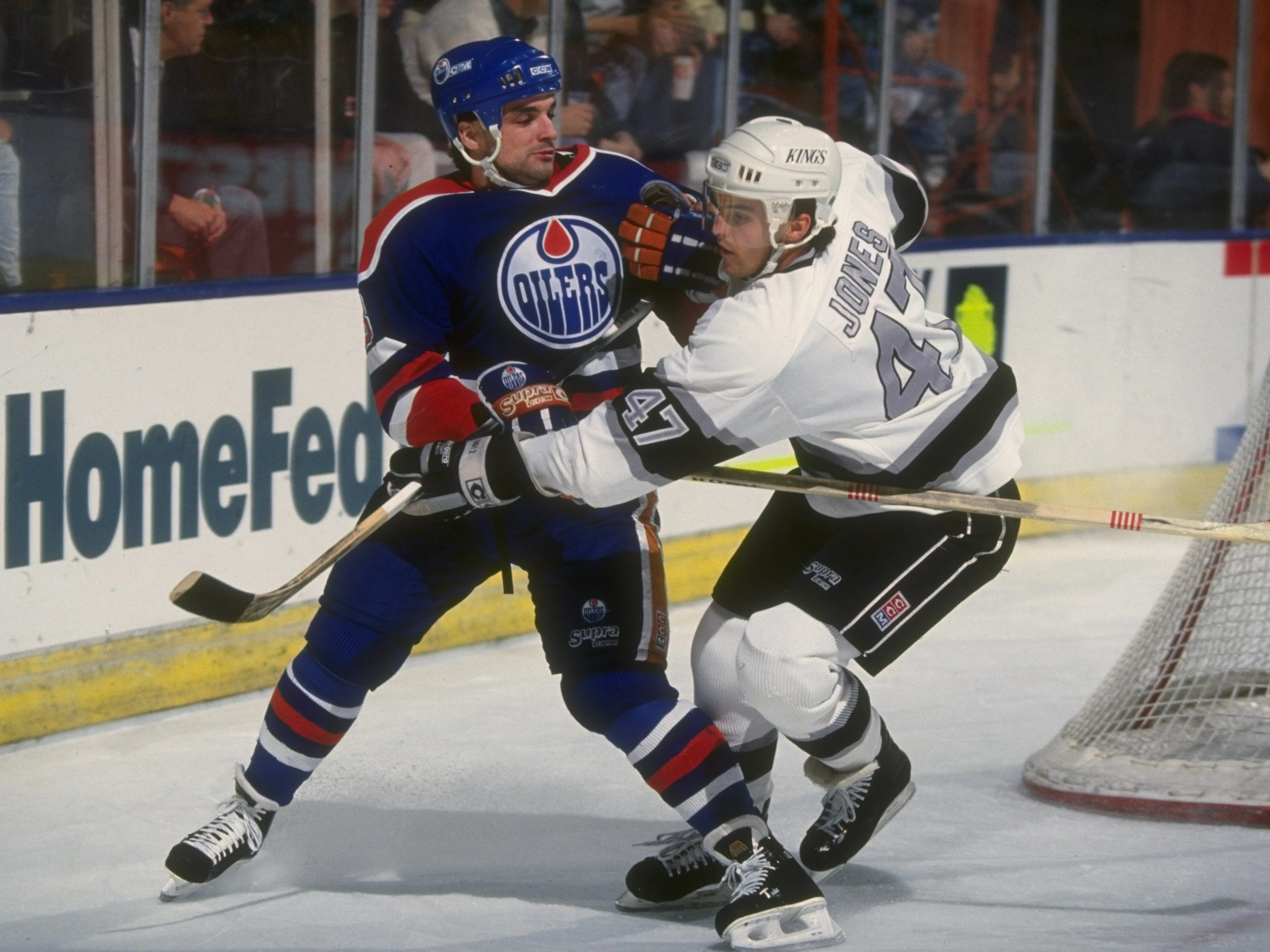 15 Dec 1990:  Rightwinger Joe Murphy of the Edmonton Oilers (left) and a Los Angeles Kings player tangle up during a game at the Great Western Forum in Inglewood, California.