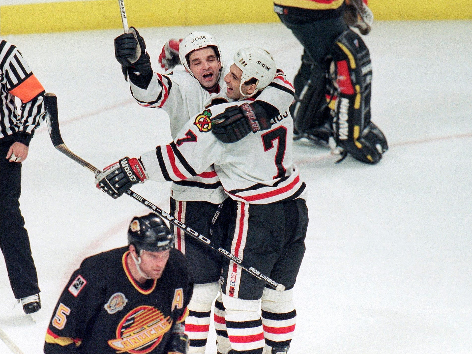 Chicago Blackhawks' Joe Murphy, left, celebrates with teammate Chris Chelios after Murphy's overtime goal lifted the Blackhawks to a 2-1 victory over the Vancouver Canucks in a second-round playoff game, Sunday, May 21, 1995 in Chicago.