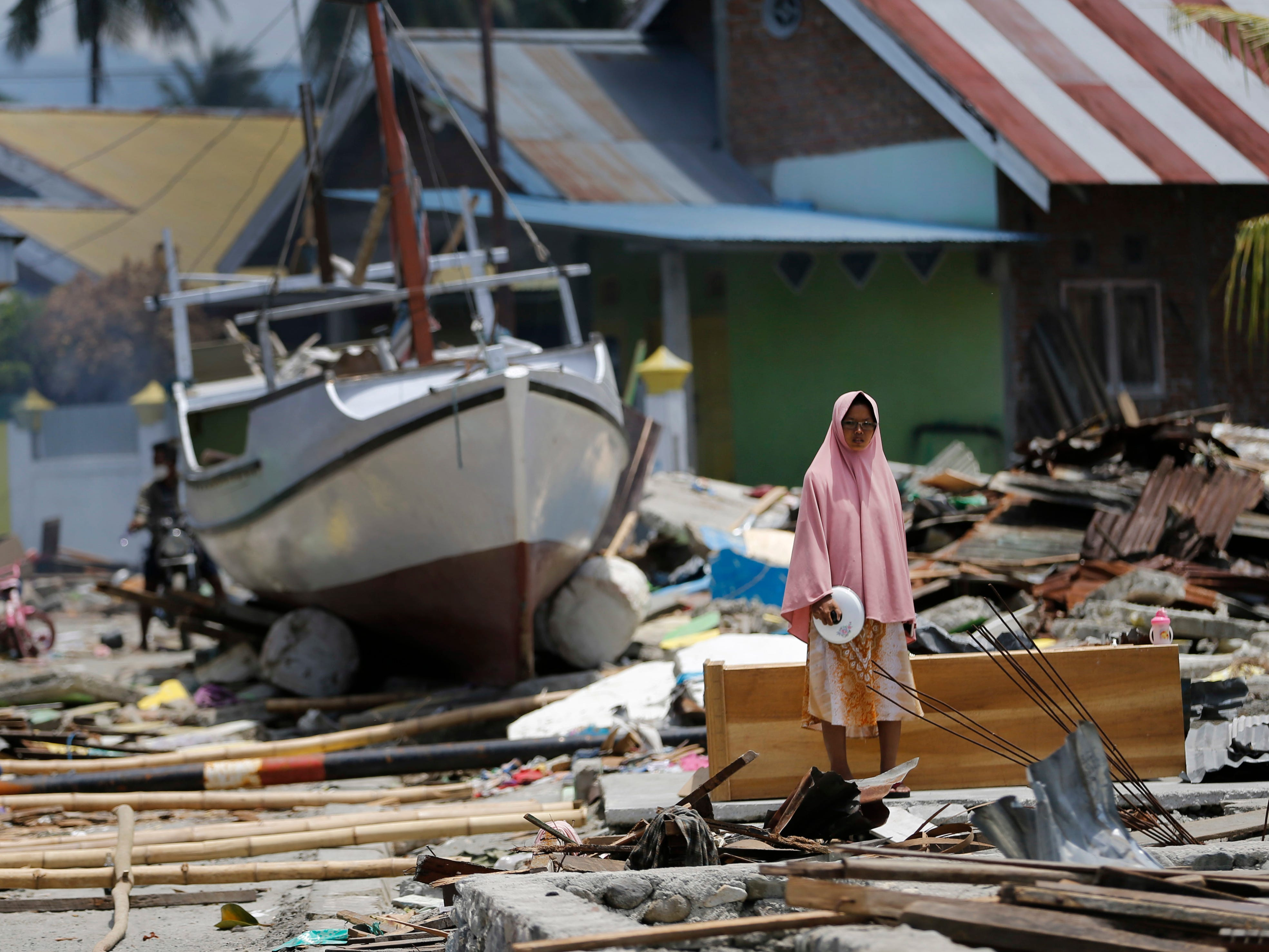 A woman stands in the rubble of houses as a boat swept ashore by tsunami rests on the ground in the background in Wani village on the outskirt of Palu, Central Sulawesi, Indonesia, Wednesday, Oct. 10, 2018. A 7.5 magnitude earthquake rocked Central Sulawesi province on Sept. 28, triggering a tsunami and mudslides that killed a large number of people and displaced tens of thousands of others.