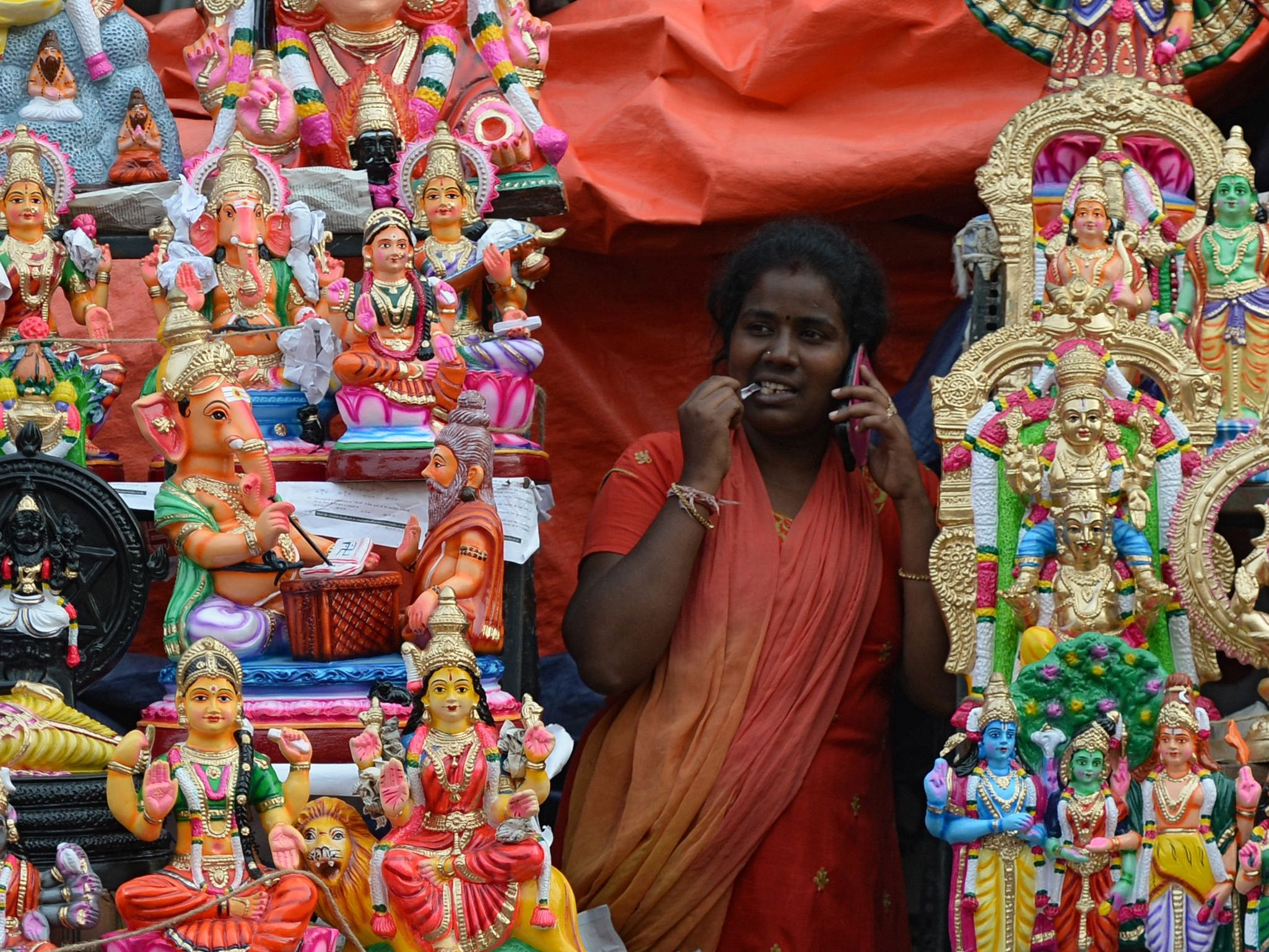 "A shopkeeper speaks on her mobile phone while at a stall selling idols of Gods and characters from the Hindu mythology used as a form of decoration during ""Navarathri"" festival celebrations, in Chennai on Oct. 10, 2018."