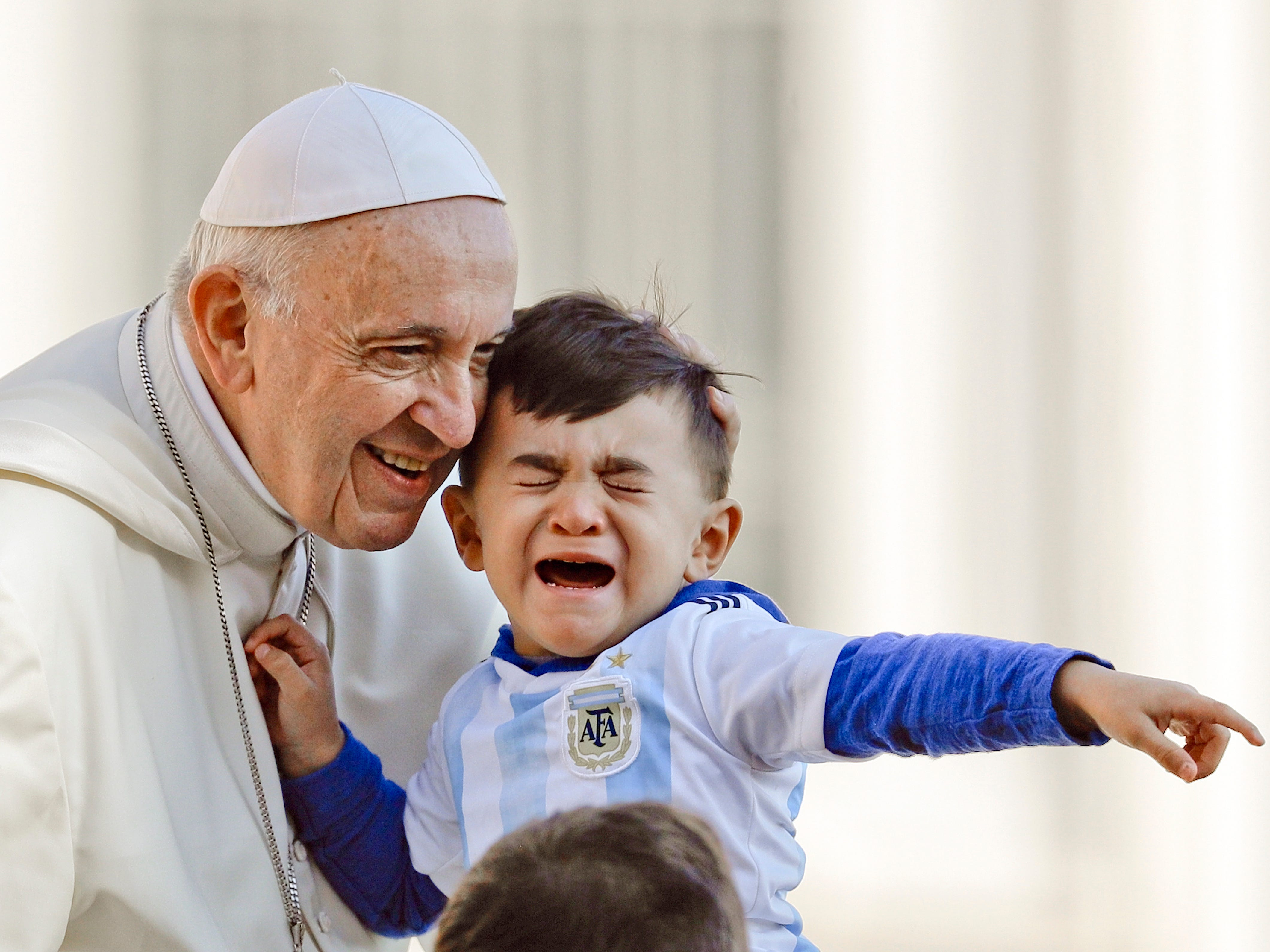 Pope Francis caresses a child as he arrives on his popemobile in St.Peter's Square for his weekly general audience at the Vatican, Wednesday, Oct. 10, 2018.