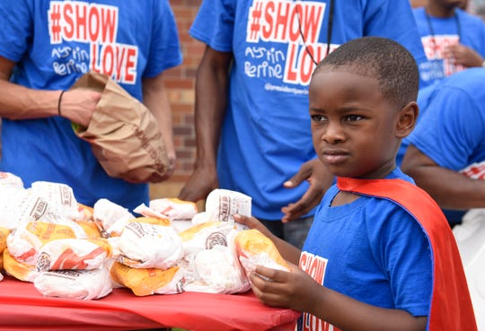 Austin Perine, 4, prepares to hand out burgers to homeless men.