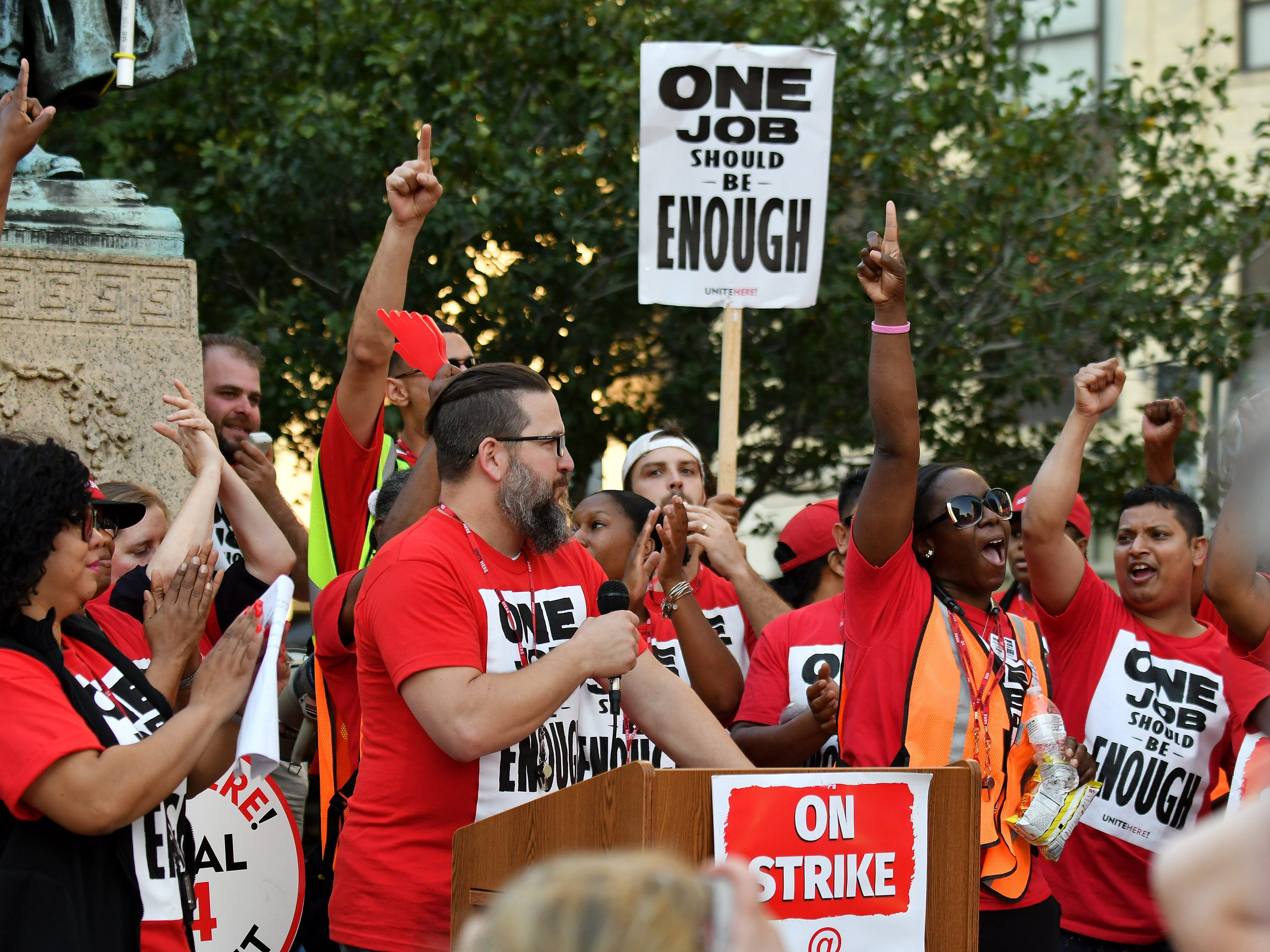 Yolanda Murray of Harper Woods, right, pointing up, and others cheer while Dave Frassetto of Royal Oak, a lead bartender at the Westin Book Cadillac, left, speaks at a rally for and by workers from Unite Here Local 24.