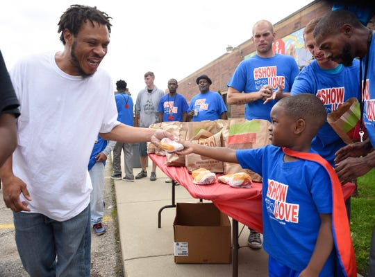 Four-year-old Austin Perine hands out a burger to Steven Brown, 36, of Inkster outside the Mariners Inn in Detroit on Wednesday.