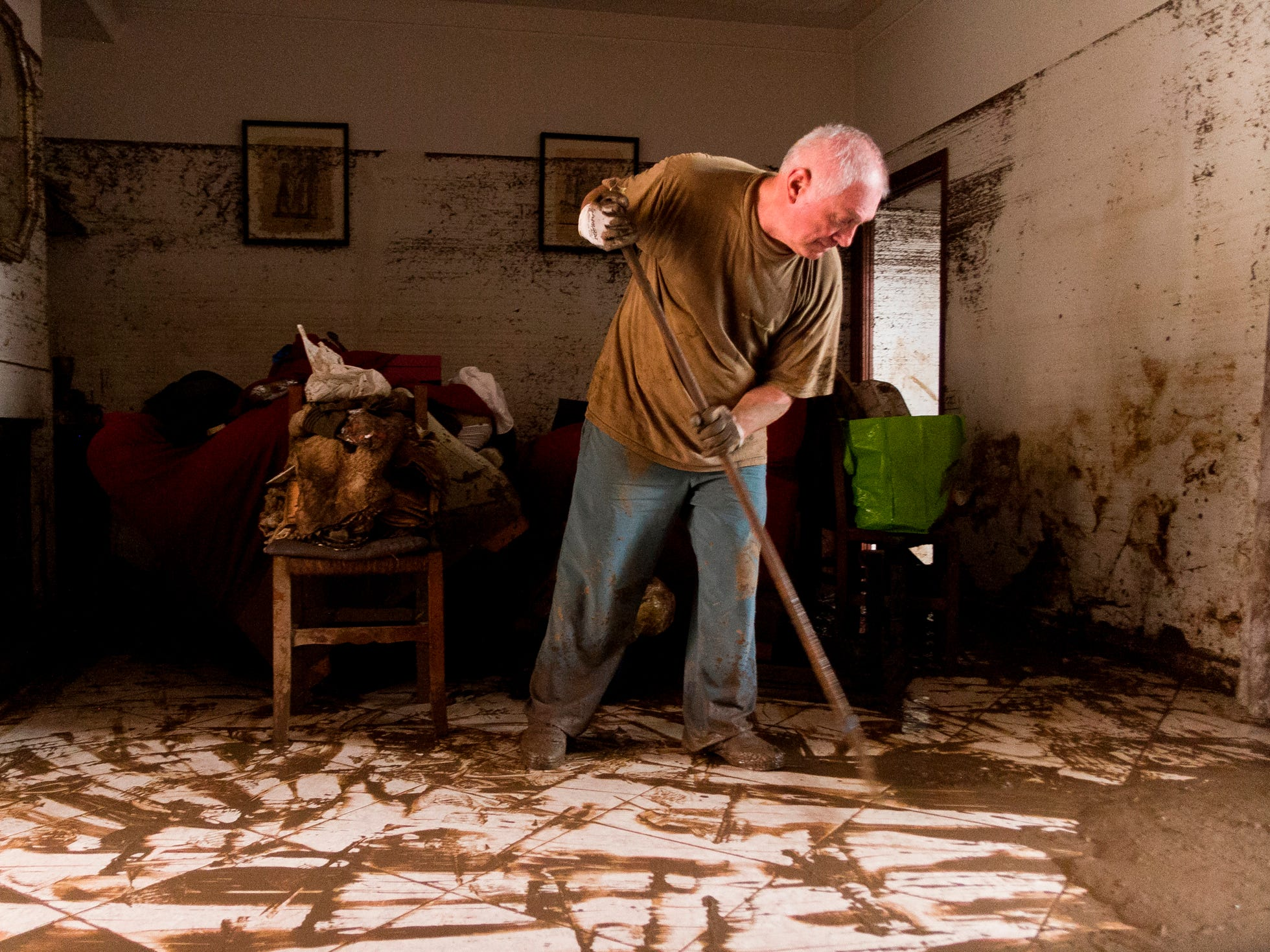 A man cleans his house after flooding in Sant Llorenc, the town hardest hit by the downpours located 40 miles east of Mallorca's capital, Palma, Spain, Wednesday, Oct. 10, 2018.