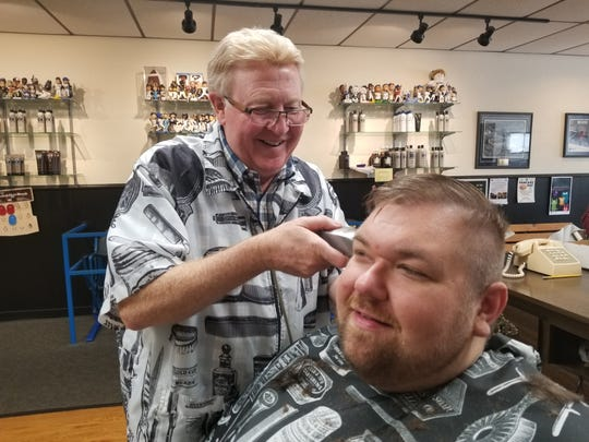 Red gives Father Ryan a quick trim; Central Barber was recognized with the 2018 Readers Choice Award for Best Barber Shop.