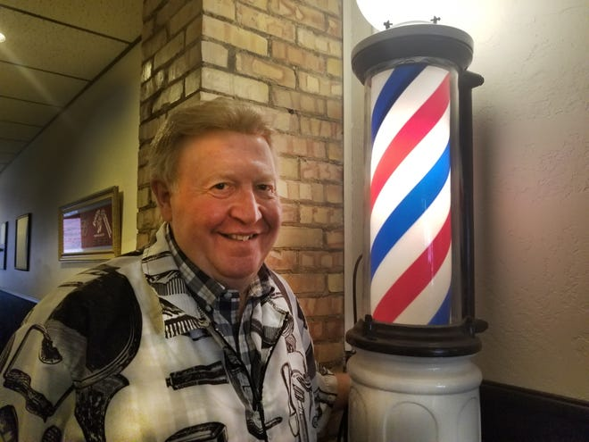 "Gary ""Red"" Muellenbach, owner of Central Barber, stands with the authentic barber pole he purchased from the American Pickers."