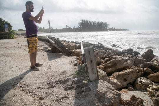 Ryan Seales of South Dakota takes video of the waves at Blind Pass on Captiva on Wednesday. The Blind Pass parking lot on Sanibel was closed due to flooding. On Tuesday the area around Blind Pass flooded at high tide.