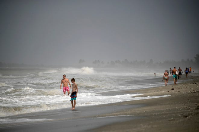 Visitors to the beach on Captiva watch the waves crash onto the shore Wednesday, Oct. 10, 2018.