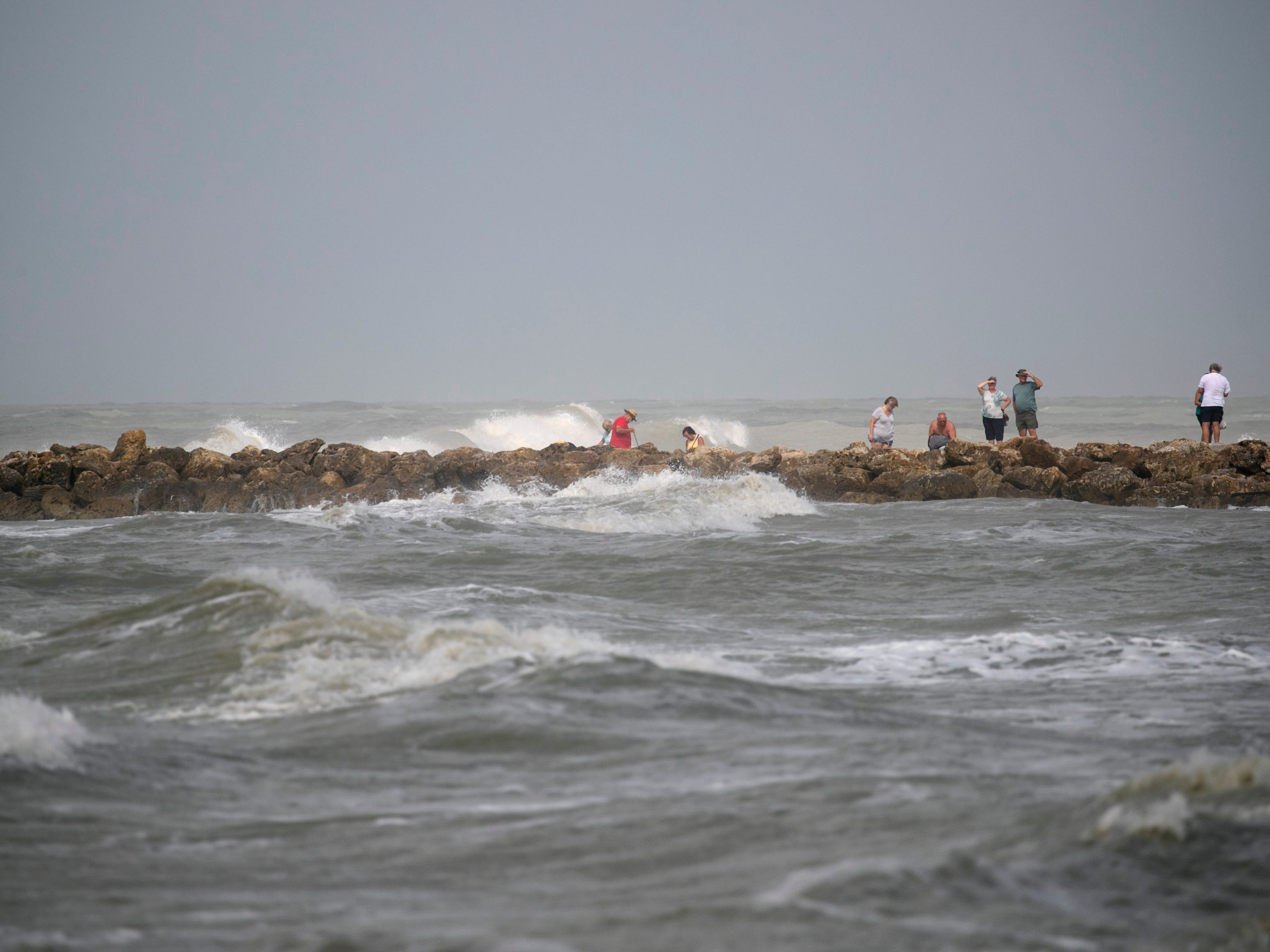 Visitors to the beach at Blind Pass on Captiva watch the waves crash onto the shore Wednesday as Hurricane Michael churned in the Gulf of Mexico heading for the Florida Panhandle.