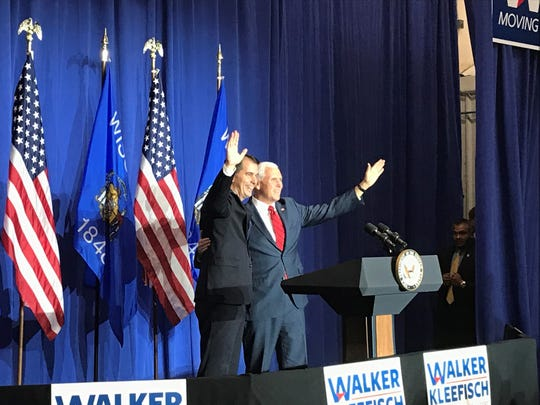 Gov. Scott Walker, left, and Vice President Mike Pence wave to the audience at a Republican rally Wednesday, Oct. 10, 2018 in Eau Claire.