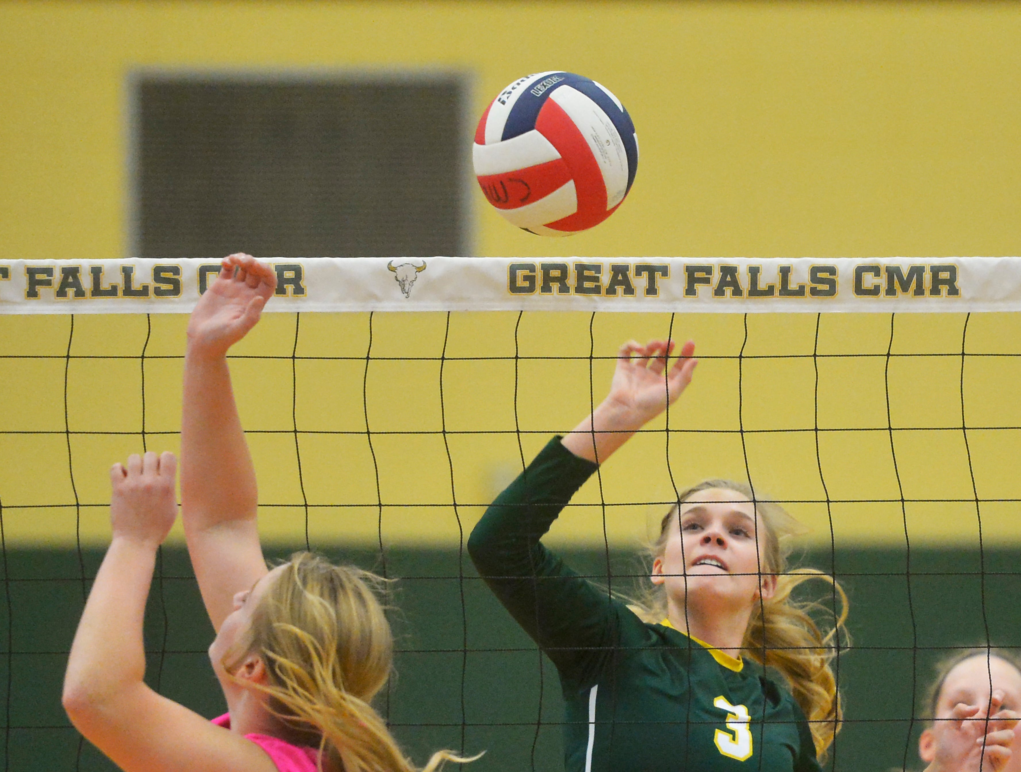 CMR's Teagan Taylor tips the ball over the net during the crosstown volleyball match in the CMR Fieldhouse, Tuesday.